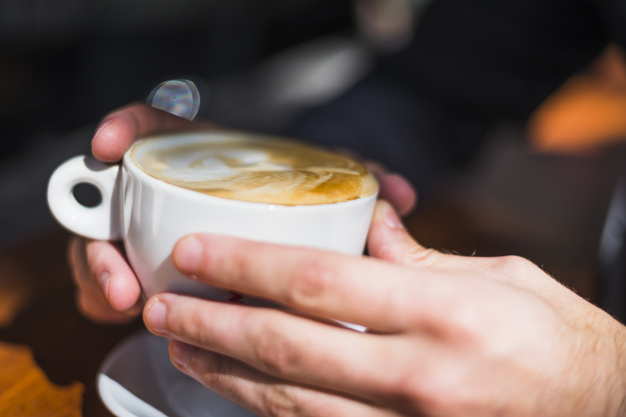 close-up-person-s-hand-holding-latte-art-coffee-cup_23-2147975370
